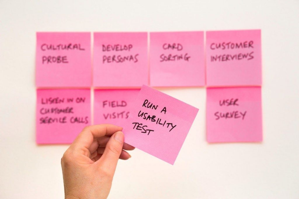 hand-putting-pink-sticky-note-on-wall-best-online-business-to-start