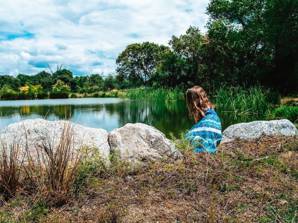 woman-sitting-at-edge-of-pond